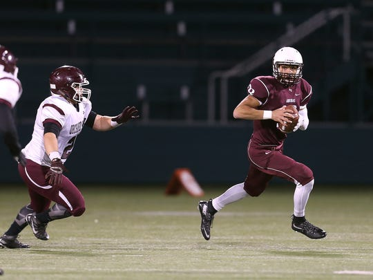 Aquinas quarterback Jake Zembiec (12) rolls away from pressure in a 42-7 win over Orchard Park. Zembiec threw for 230 yards and 4 touchdowns.