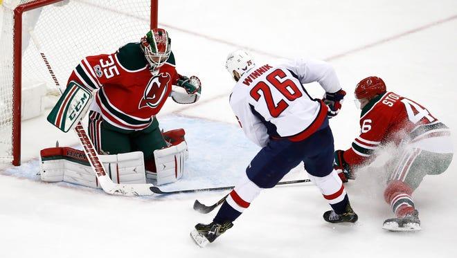 Washington Capitals left wing Daniel Winnik (26) attacks against New Jersey Devils goalie Cory Schneider (35) as defenseman Karl Stollery (46) defends during Thursday's game.