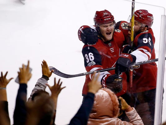 Arizona Coyotes right wing Christian Fischer (36) celebrates his winning goal against the Los Angeles Kings with defenseman Jason Demers, right, during overtime of an NHL hockey game Friday, Nov. 24, 2017, in Glendale, Ariz. The Coyotes won 3-2. (AP Photo/Ross D. Franklin)