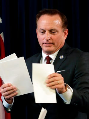 In this Dec. 19, 2016, file photo, Iowa Secretary of State Paul Pate collects ballots during Iowa's Electoral College vote at the Statehouse in Des Moines. Pate did not disclose his role in a newly-formed company that has spent around $2 million opening a self-storage rental business and purchasing a strip mall, according to a review by the Associated Press.