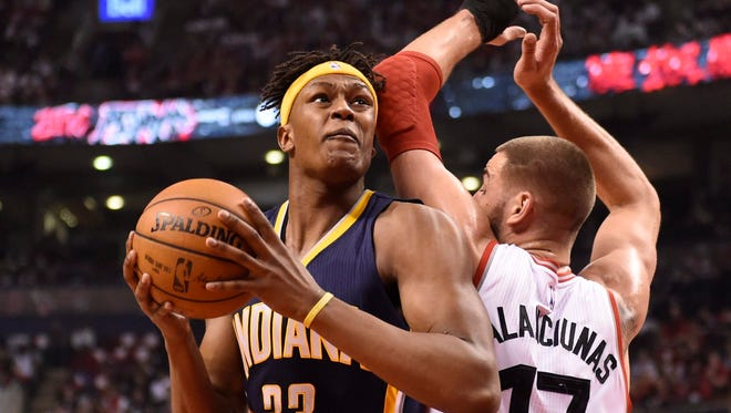Indiana Pacers' Myles Turner (33) moves around Toronto Raptors' Jonas Valanciunas  as he drives to the basket during the first half in Game 1 in the first round of the  NBA  playoffs Saturday, April 16, 2016, at Toronto