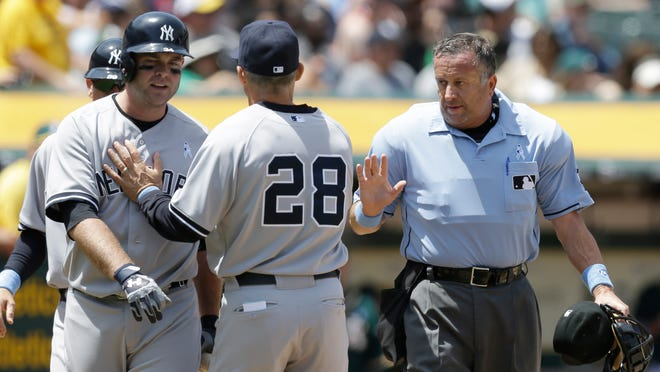 New York Yankees catcher Brian McCann (left) is separated from home plate umpire Dale Scott (right) by manager Joe Girardi in the fourth inning against the Oakland A's on Sunday. McCann was arguing a called third strike.