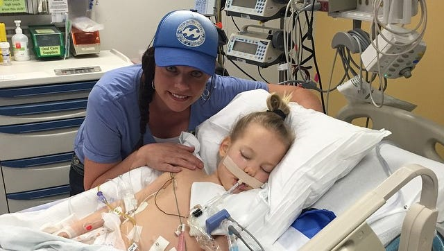 Gwen Peterson, the facilitator of the Kisses For Kycie Facebook page, takes a photo with Kycie Terry as she rests in Primary Children's Hospital Wednesday, July 1, 2015.