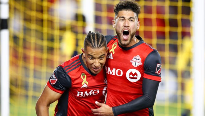 Toronto FC's Justin Morrow (left) celebrates with teammate Jonathan Osorio after scoring against the New York Red Bulls in the second half at BMO Field.
