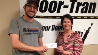 Rob Esposito, owner of the Sturgeon Bay Jimmy John's, gives a check to Pam Busch, Door-Tran Mobility manager.