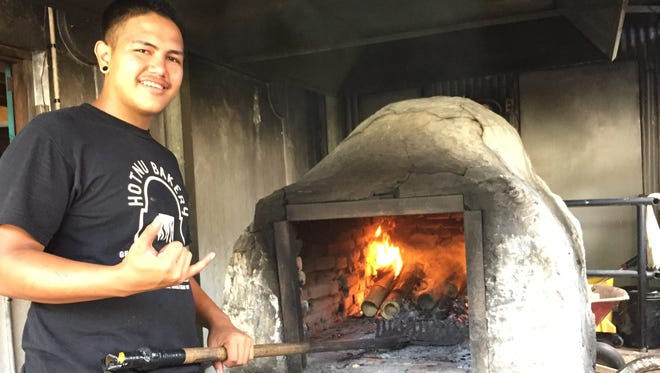 Donovan Flores, 18, stokes the fire at the Hotnu Bakery in Inarajan.