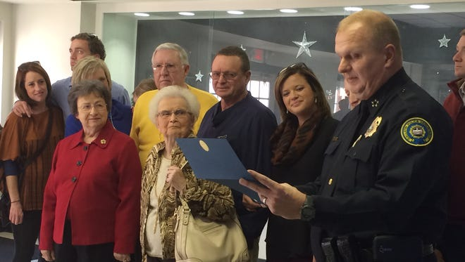 "Gallatin Police Chief Don Bandy, right, reads a certificate honoring Dr. Jerry McMillan (back row, center right) and his actions to save James ""Hack"" Gillum (back row, center left) during a Nov. 24 Lions Club meeting."