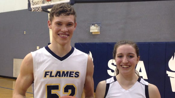 Shalom Christian's Jonah Stains, left, and Lydia Harris pose together after both scoring their 1,000th-career point on Monday night in victories over Grace Academy.