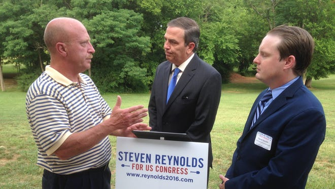 Democratic congressional candidate Steven Reynolds of Murfreesboro, center, joins campaign manager Darrell Bouldin, right, in listening while Stephen Durham talks about issues.