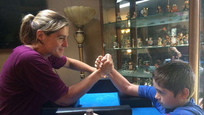 Shawna Feist demonstrates her arm wrestling technique with one of her sons, Peyton.