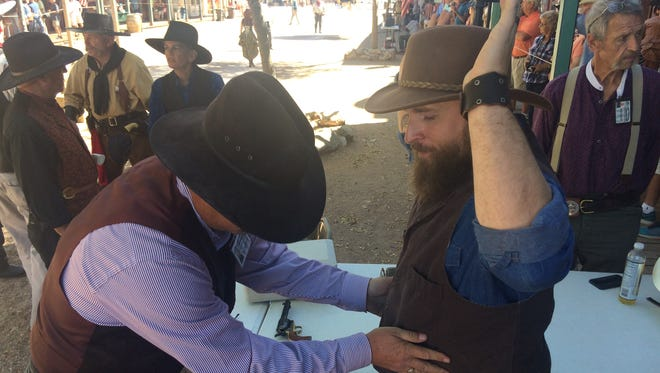 Duane Brown inspects the weapons of Ryan Horback, dressed as Doc Holliday, before a performance of the Goose Flats Gunslingers along Allen Street in Tombstone on Oct. 20, 2017. Brown's role as armorer and the inspections are mandated under a city ordinance.