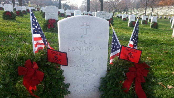 Flags of the United States and Rutgers University were added to wreaths placed at the Arlington National Cemetery grave of alumnus and World War II veteran Paul Bangiola as part of the Rutgers alumni chapter in Washington's contribution to the Wreaths Across America program in 2015.