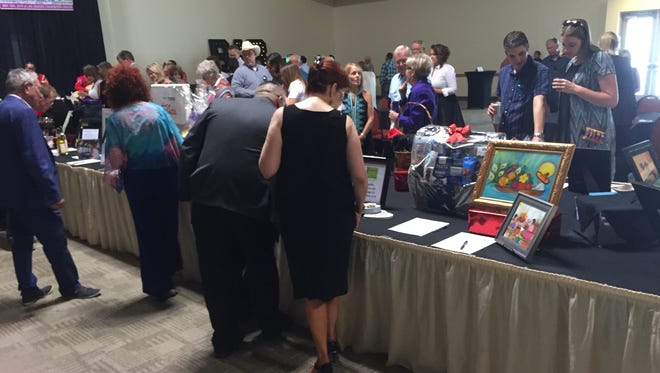 Those attending a fundraiser for Project Link, a program to help homeless students in Las Cruces, check out the items for sale on the silent auction table Thursday, May 10 at the Las Cruces Convention Center.