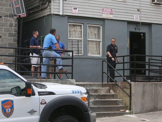 Police conduct an investigation at 210 Washington Street