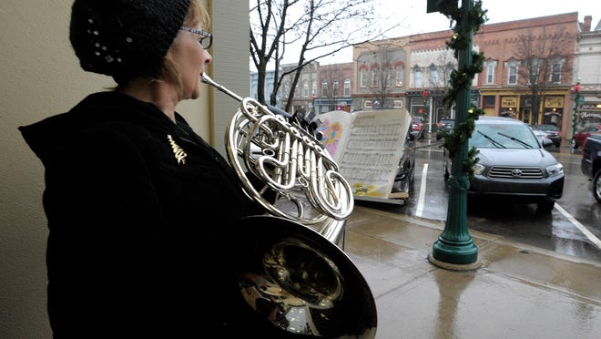 Claire Sprau, 56, of Ann Arbor, plays Christmas music on her French horn in front of the Dexter Bakery. Sprau plays in the town band. Dexter, near Ann Arbor, is Michigan's newest city.
