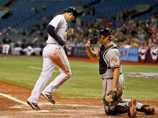 Tampa Bay Rays' Evan Longoria (3) scores on a bases-loaded walk by Baltimore pitcher Brian Matusz.