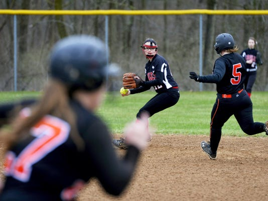 Dover's Cassandra Root, center, prepares to throw to first base as York Suburban's Brooke Day, right, runs into an out at second base and Emmy Turybury, left, races towards first during Friday's game at Dover High School.