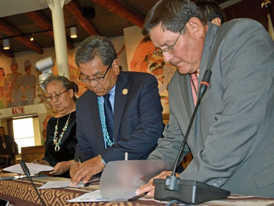 Acting Chief Justice Eleanor Shirley, left, Navajo Nation President Russell Begaye and Speaker LoRenzo Bates sign an agreement that establishes nine priorities for the tribe during the opening of the Navajo Nation Council's summer session on Monday in Window Rock, Ariz.