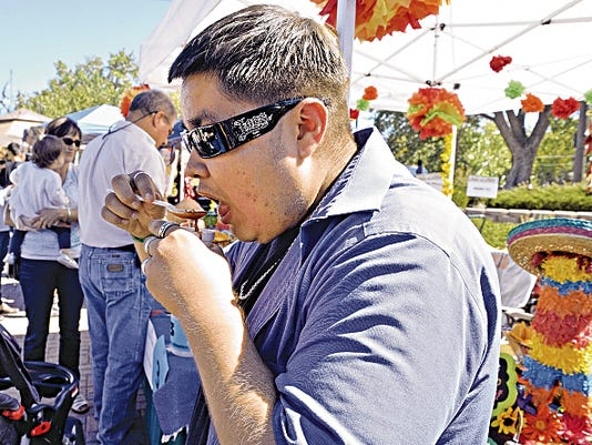 Marco Hernandez, of Farmington, tries out Monica Schultz's pork red chile at the Chile in October cook-off last year at Berg Park in Farmington.