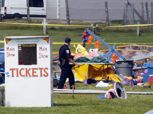 Investigators inspect the site of a circus tent that collapsed Monday during a show by the Walker Brothers International Circus at the Lancaster Fair grounds in Lancaster, N.H. Tuesday, Aug. 4, 2015. A quick moving storm with 60 mph winds hit the tent shortly after the show started killing a father and daughter. (AP Photo/Jim Cole)