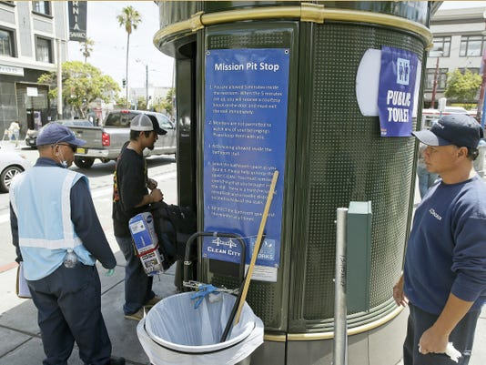 In this Thursday, July 30, 2015, photo an attendant looks on as a man enters a Pit Stop public toilet outside a Mission District transit station in San Francisco. The Pit Stop, located by a public wall covered with a repellant paint that makes pee spray back on the offender, is a project operated by San Francisco Public Works that provides portable toilets and sinks and is part of the city's latest attempt to clean up urine-soaked alleyways and walls. (AP Photo/Eric Risberg)