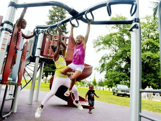 From left, Janyse Trust, 6, watches as Anastasia Hawkins, 9, and her sister Angelina Hawkins, 5, play on one of two new playscapes at Penn Park on Wednesday before a dedication ceremony. Years-long efforts to update the park, which is the city's largest and oldest green space, have culminated in two new playscapes and a splash pad.