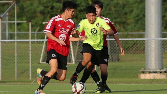 Bank of Guam Strykers' Joshua Calvo attempts to get through Wings Black defenders en route to the goal during an opening week U18 division match of the Aloha Maid Minetgot Cup Elite Youth League Monday at the Guam Football Association National Training Center. The Strykers won 3-2.