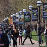 Students walk along South State Street through the Ann Arbor campus of the University of Michigan.