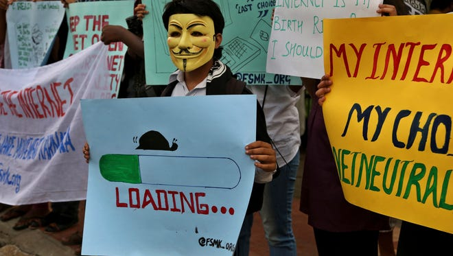 An activist wears a mask as he holds a placard during a demonstration supporting net neutrality in Bangalore, India in 2015.