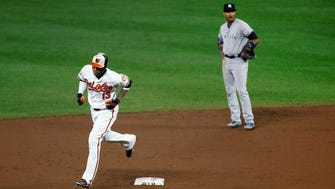 Baltimore Orioles' Manny Machado, left, rounds the bases past New York Yankees second baseman Starlin Castro after hitting a two-run home run during the ninth inning of a baseball game in Baltimore, Wednesday, Sept. 6, 2017. Baltimore won 7-6.
