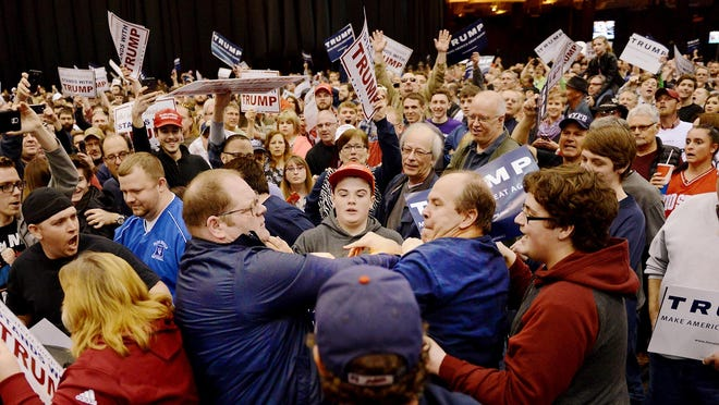 FILE - A protester, center left, and a Trump supporter, center right, scuffle during a rally for Republican presidential candidate Donald Trump Saturday, March, 12, 2016, held at the I-X Arena in Cleveland, Ohio.