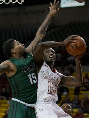 New Mexico State guard Sidy N'Dir drives the baseline and gets fouled by Eastern New Mexico's Jamari Pierce during the opening minutes of the second half Tuesday night at the Pan American Center.