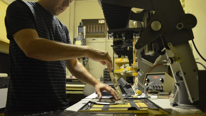 Mike Stenerson, a photographer at the University of Iowa's Center for Media Production, works in the darkroom Thursday in Seashore Hall. The center, which has been chronicling university happenings for decades, is closing Monday.