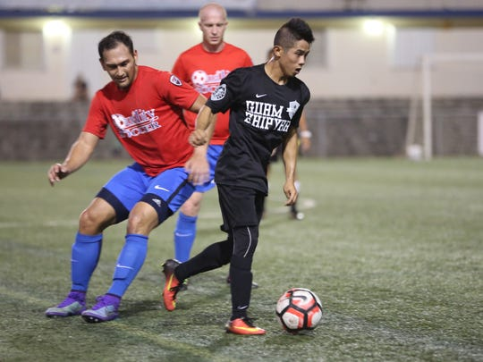 Haya United's Sydney Talledo sprints with the ball past Quality Distributors defender Regis Cavalie in a Premier Division match of the Budweiser Soccer League Dec. 3 at the Guam Football Association National Training Center. Quality defeated Haya United 8-0.