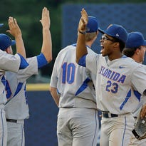 Florida's Buddy Reed high-fives teammates after the Gators beat LSU 2-1 in the SEC baseball tournament on Saturday in Hoover, Ala.