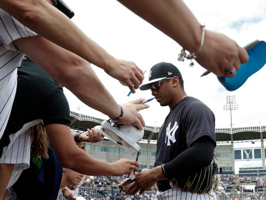 Seattle Seahawks quarterback Russell Wilson gives autographs before a baseball spring exhibition game between the New York Yankees and the Atlanta Braves, Friday, March 2, 2018, in Tampa, Fla. Wilson pinch hit for the Yankees and struck out in the fifth inning. (AP Photo/Lynne Sladky)
