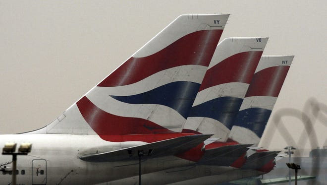 This is a  Wednesday, Dec. 16, 2009. file photo of British Airways plane tail-fins are seen behind barbed wire at Heathrow Airport in London, British Airways cabin crew are to strike for three days from March 20 and for four days from March 27 in a long-running row over cost-cutting, Unite union  announced Friday March 12, 2010.(AP Photo/Kirsty Wigglesworth)