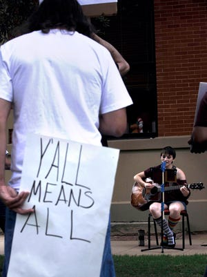 """Jake Lanehart holds a sign while listening to Jessica Schultz perform Saturday at Everman Park Sept. 16, 2017. The March Against Hate started at City Hall and ended here with about 25 people attending. Lanehard said of his sign, """"We're southern and (y'all) is what we like to say, but it has never meant everybody. We need to change it."""" This was Schultz's first time performing in public. """"I've always wanted to perform, this is my first performance but it was for a good cause,"""" she said."""