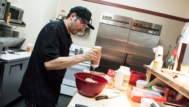 Chef Anthony Geraci pours a homemade honey mustard sauce into a bowl while making tuna salad at the Hidden Corner Café on Thursday, May 24, 2018.