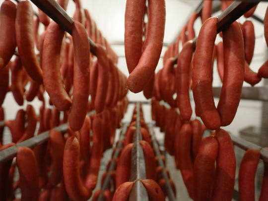 Racks of wieners are hung at a Newton Meats cooler