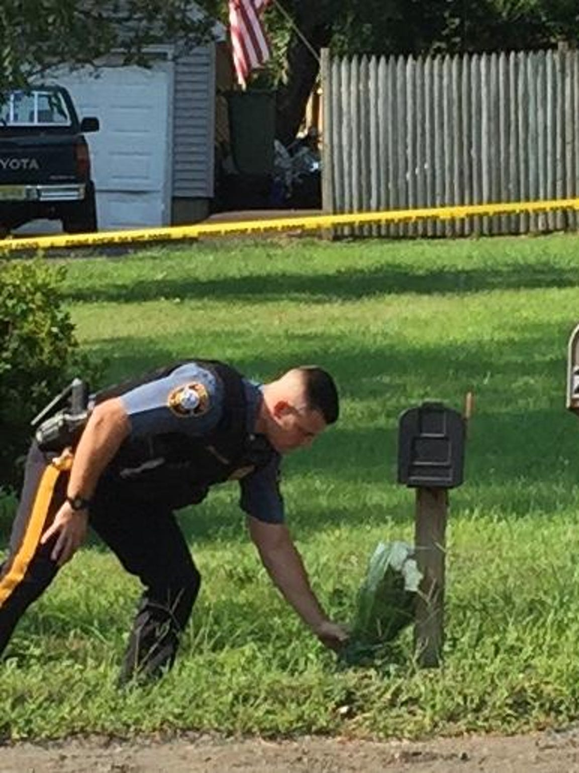 A Warren Township police officer places flowers beside the mailbox of Heidi Lynn Errickson's home on Aug. 17, a day after Errickson and her brother were killed by her fiance.