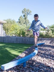 Scott Gottlieb walks the balance beam in his family's backyard. The beam and a nearby swing set, which were salvaged from a nearby school, help define the play area, where Kuty and Gottlieb also installed artificial turf that requires no water and holds up better than lawn.