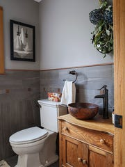 A shared powder room between the two homes has slate tile with small copper cut-outs.