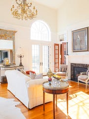 In the formal living room, an 18th-century French chandelier and custom English wall paneling add a touch of years gone by.