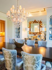 Triple crown moulding with metallic gold accent paint adds interest to the ceiling, which is painted in a serene blue.