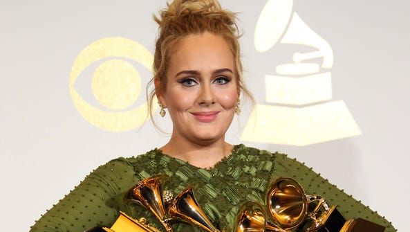 Adele poses with her five awards in the photo room