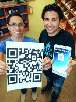 Daniel Cisneros, left, and Esai Lopez, both 17, hold up a tablet and a QR code in the  Santa Teresa library on Friday. The pair created a mobile app that was designed to encourage student participation in school events. Students can download the app, named Warrior Rewards, check it at school functions and win prizes