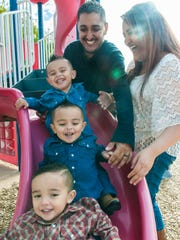 Javier and Valerie Artiaga play with their triplets