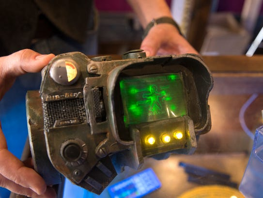 Steve Clark displays a mock-up of a Pip-Boy from the video game series Fallout that he made for his son and is displaying at his store, Tales of Tomorrow.