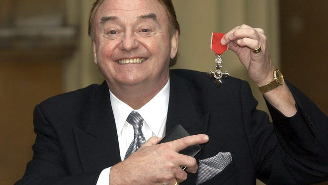 """Gerry Marsden holds his MBE after being knights in December 2003. Marsden, the British singer and lead singer of Gerry and the Pacemakers, who was instrumental in turning a song from the Rodgers and Hammerstein musical """"Carousel"""" into one of the great anthems in the world of football, has died. He was 78."""
